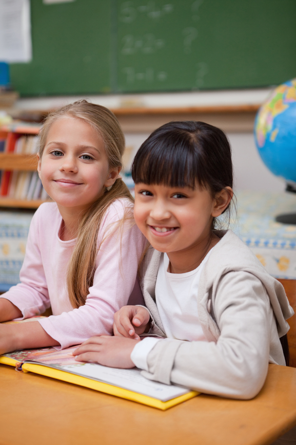 Portrait of smiling schoolgirls reading a fairy tale